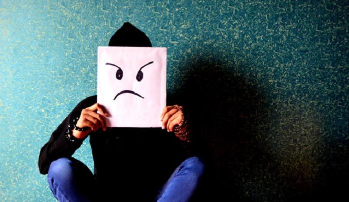 סדר במחשבות: איש מחזיק מול פניו ציור של פנים כועסות