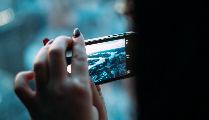 אישה מחזיקה טלפון חכם ומצלמת