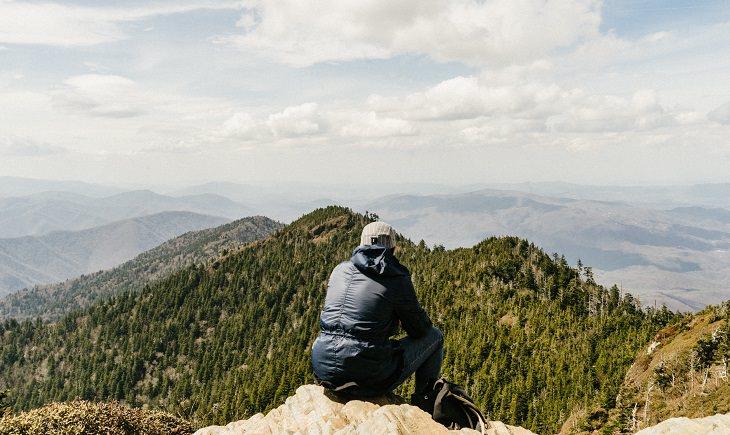 איש יושב על צוק ומסתכל על נוף הררי ומיוער