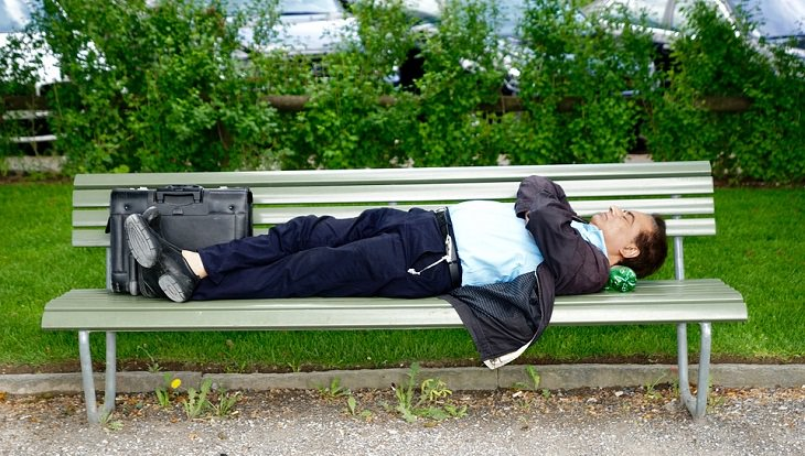 גבר בחליפה ישן על ספסל בפארק