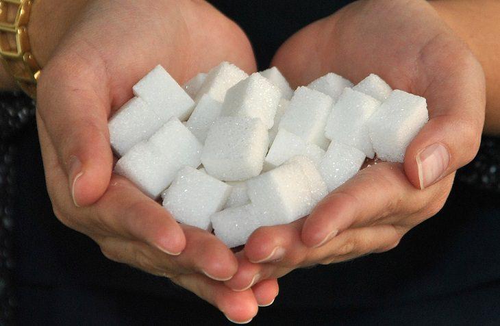 טיפול טבעי לסוכרת - אסכרקס: זוג ידיים מלאות בקוביות סוכר