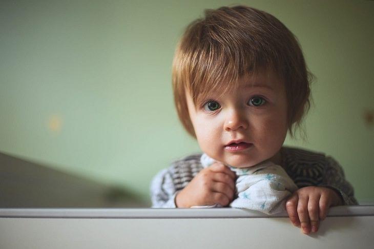 יתרונות בריאותיים של הקיווי: ילד עומד, אוחז במעקה מיטה ומביט במצלמה