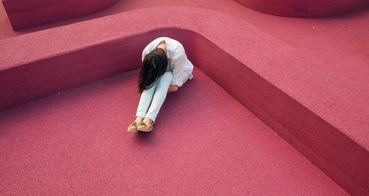 מיתוסים לגבי לחץ: אישה יושבת מכופפת סביב קירות מבוך ורודים