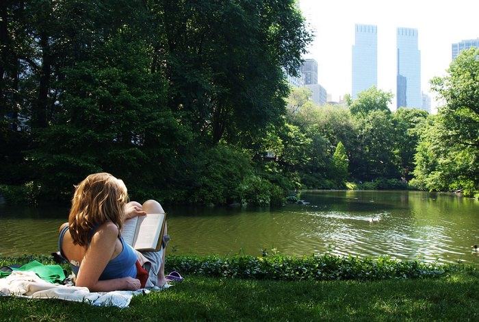 אישיה שוכבת בפארק וקוראת