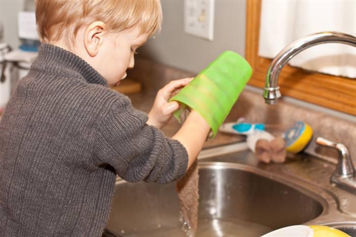 פיתוח ביטחון עצמי בריא בילדים: ילד שוטף כלים מעל כיור המטבח