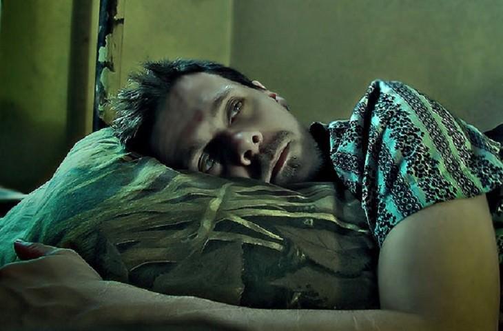 גבר שוכב במיטה עם עיניים פקוחות