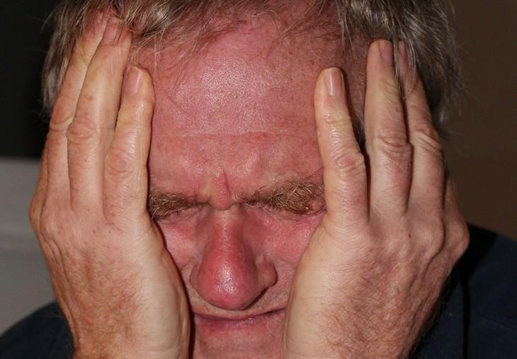 אדם מחזיק את ראשו וסובל מכאב בצדדים