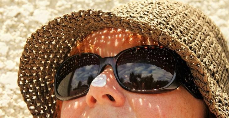 אישה עם כובע קש ומשקפי שמש