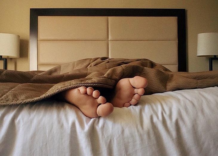 כפות רגליים מציצות מתחת לשמיכה