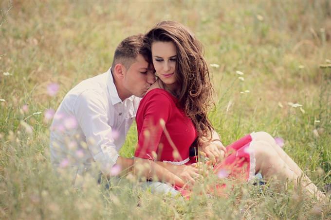 גבר מנשק כתף של אישה בשדה פרחוני
