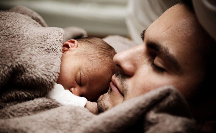 אב צעיר ישן ומחזיק את בנו התינוק שישן עליו