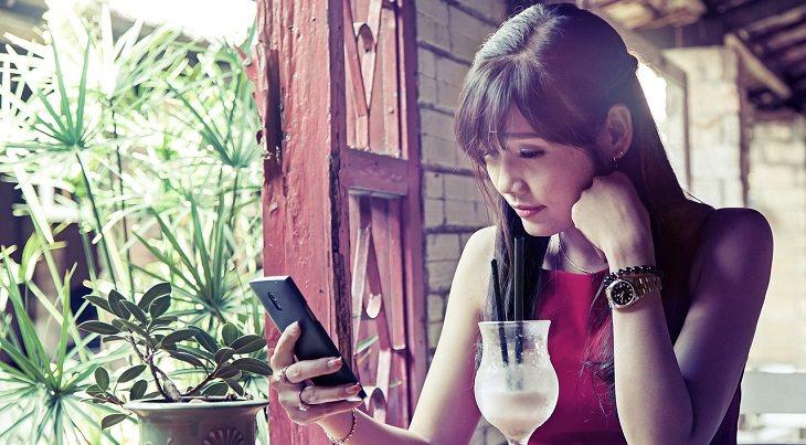 אישה יושבת עם סמארטפון