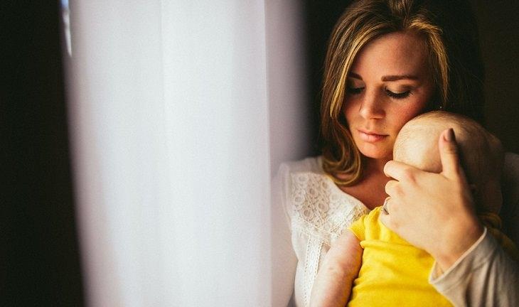 אם מחזיקה את תינוקה ומניחה את ראשו על כתפה