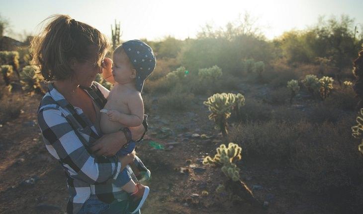 אם מחזיקה את בנה התינוק על הידיים בפרדס ומחייכת אליו