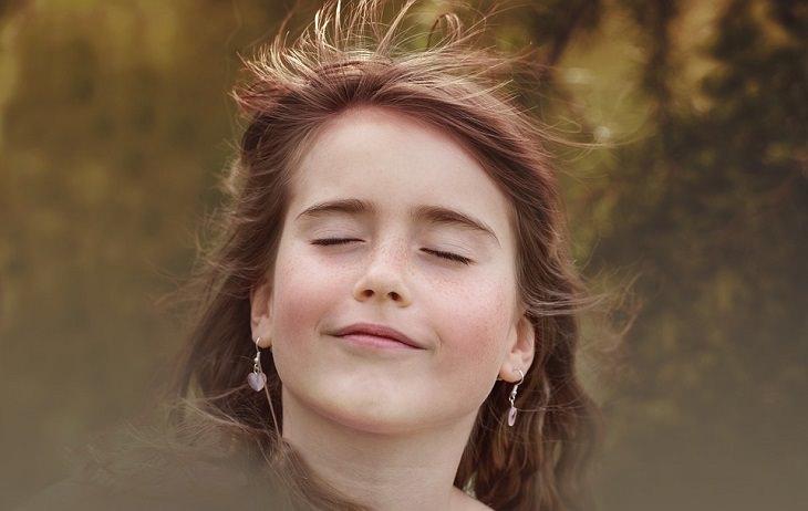 אישה עוצמת עיניים ונושמת מול הרוח