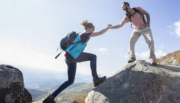 גבר עוזר לאישה לעלות על סלע גבוה