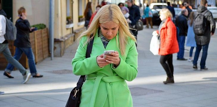 עצות להצלחה של ג'ק מא: אישה מסתכלת בטלפון ברחוב