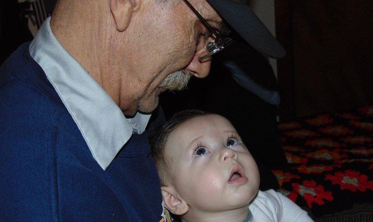 טיפים לחיים מאושרים בגיל הפרישה: איש מבוגר מסתכל על נכדו התינוק
