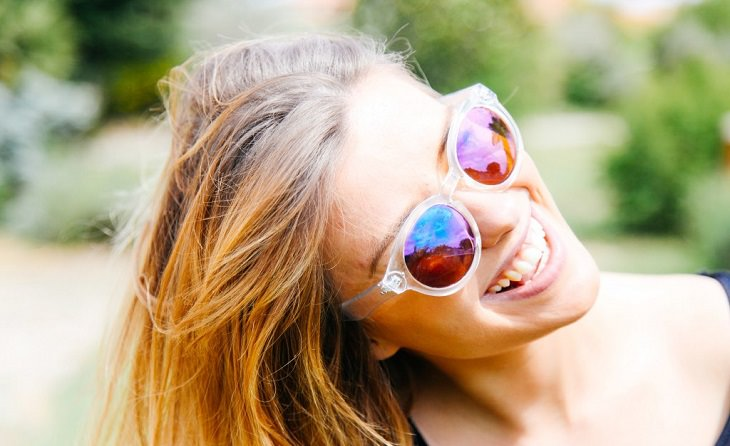 דרכים לריפוי הגוף בעזרת המחשבה: אישה מחייכת עם משקפי שמש
