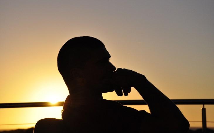 דרכים לריפוי הגוף בעזרת המחשבה: צללית של אדם יושב וחושב כשהוא מניח את ידו על אזור הסנטר