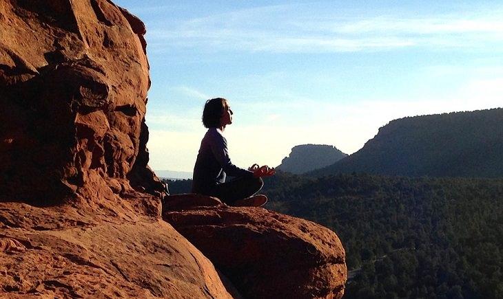 דרכים לריפוי הגוף בעזרת המחשבה: אישה יושבת ומתרגלת מדיטציה על צוק של הר