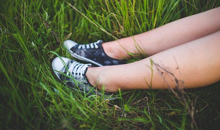 רגליים של אישה מונחות על דשא