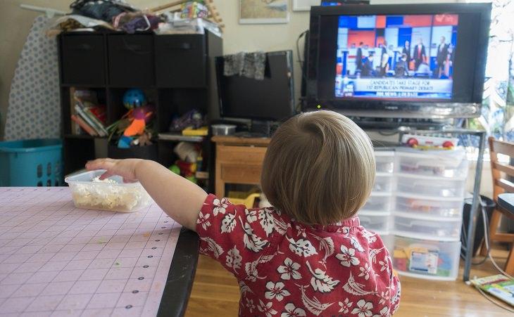ילד שולח יד אל קערת חטיפים בזמן צפייה בטלוויזיה