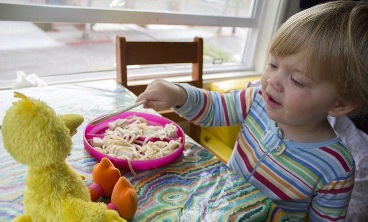 ילד מאכיל את הבובה שלו