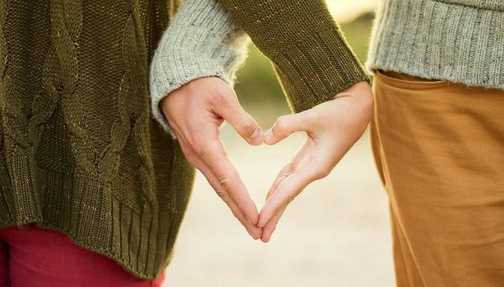 זוג יוצר צורה של לב עם כפות הידיים