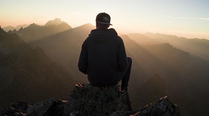 אדם יושב על פסגת הר וצופה אל האופק