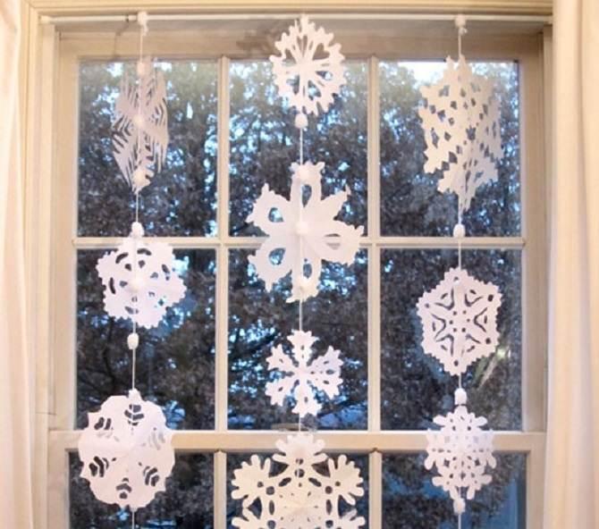 פתיתי שלג מנייר תלויים מול החלון עם חוט