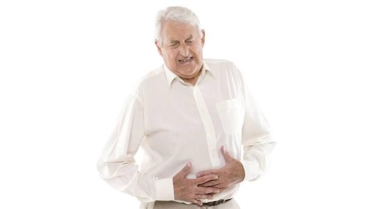 אדם מבוגר שמחזיק את הבטן שלו ונראה כסובל