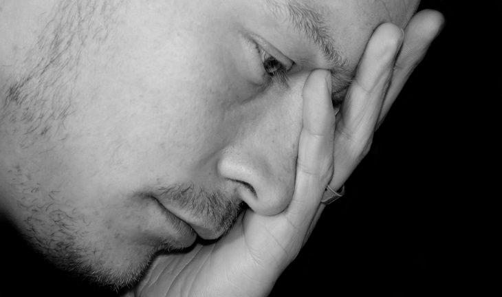 8 סימנים למחסור בסידן: גבר שם יד על אזור המצח בייאוש