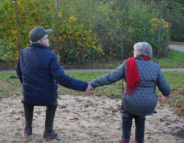 זוג מבוגר ישוב על נדנדות ומחזיק ידיים