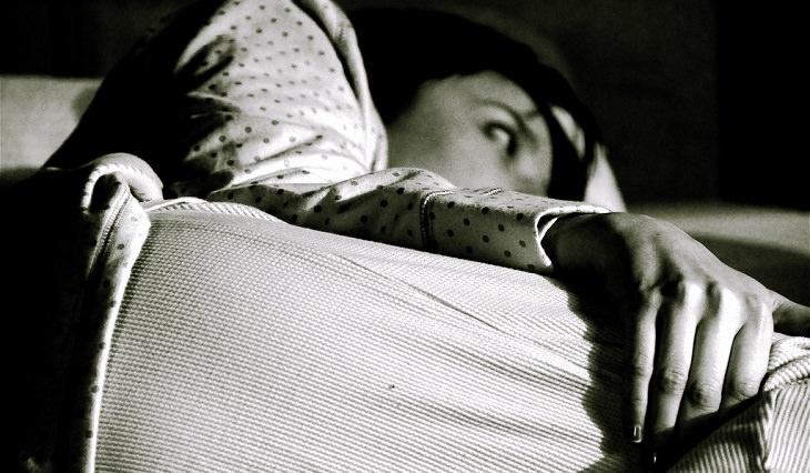 8 סימנים למחסור בסידן: אישה שוכבת ערה במיטה