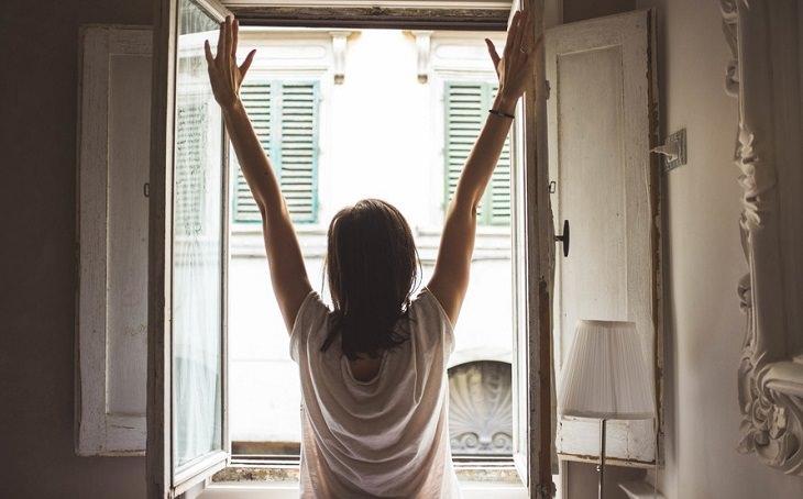 אישה עומדת מול החלון בבוקר ומתמתחת