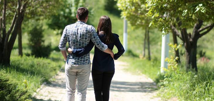 גבר ואישה מחובקים מסתכלים למרחק באזור פורח וירוק