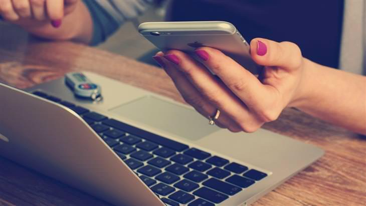 יד של אישה מחזיקה סמארטפון בזמן שהיא משתמשת גם במחשב