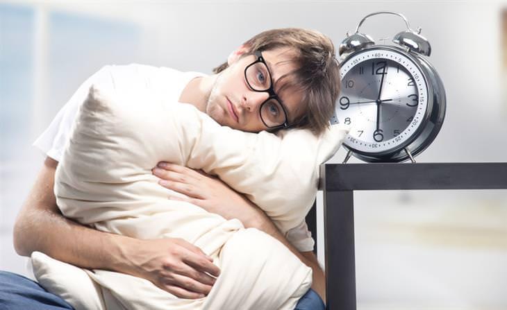 גבר מחבק כרית ונראה תשוש ליד שעון שמסמל על השעה 00:30