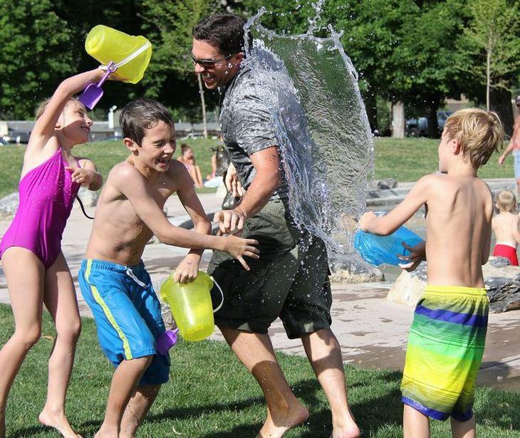 ילדים בבגדי ים משפריצים מים על אביהם שבבגדים רגילים