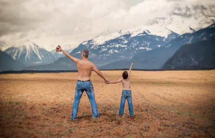 אב וילד בחיק הטבע מרימים את ידיהם לשמים ומחזיקים ידיים