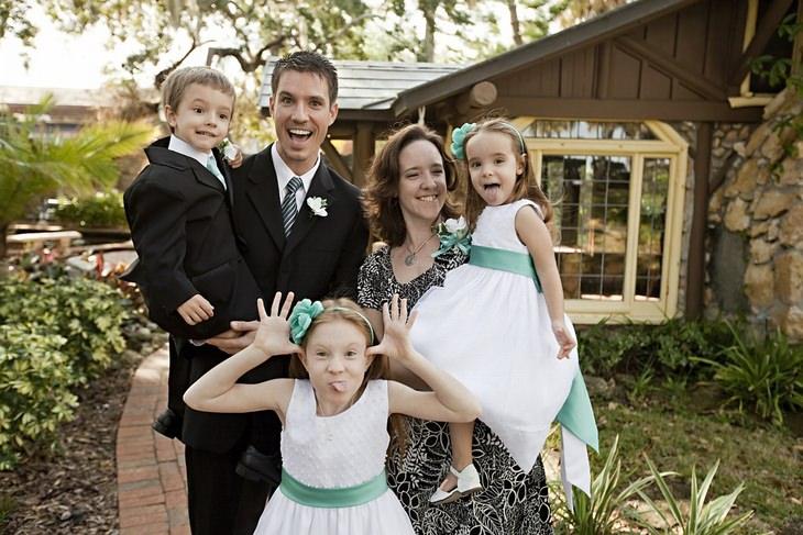 אבא, אמא ו-3 ילדים לבושים בבגדים יפים ועושים פרצופים מצחיקים