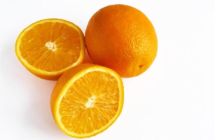תפוזים מונחים על משטח לבן