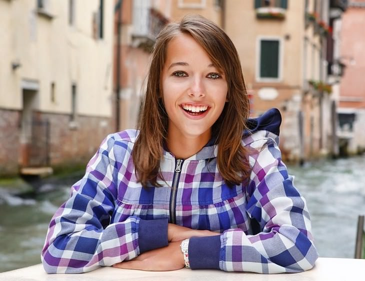מאכלים להלבנת שיניים: אישה צעירה מחייכת חיוך רחב