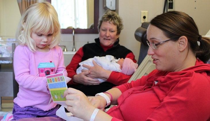 שיטה לדיבור עם ילדים באופן שעוזר להם להצליח בחיים: אמא מקריאה לילדה כרטיס ברכה