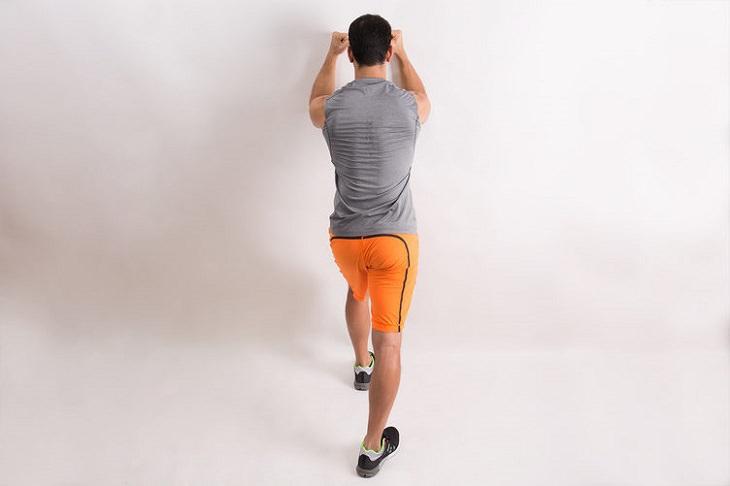 תרגילים איזומטריים: צילום אחורי של אדם מצמיד אגרופים לקיר