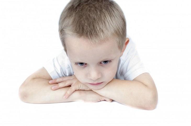 ילד מהורהר נשען בשכיבה על ידיו