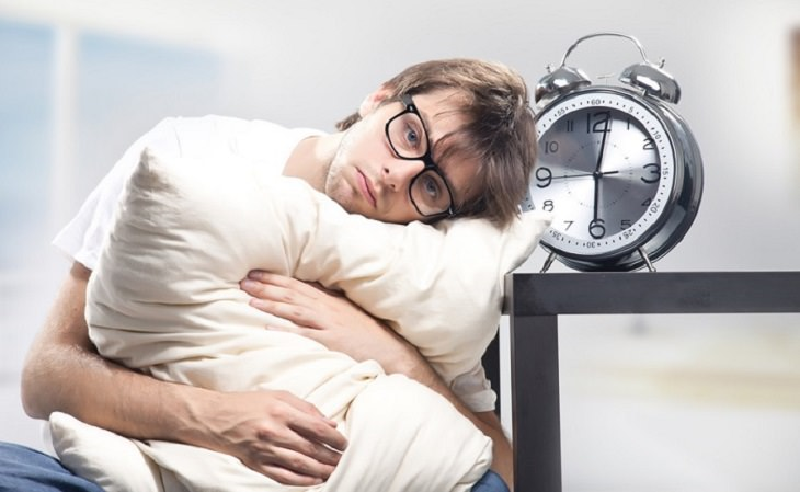 גבר עייף מחבק כרית ליד שעון מעורר