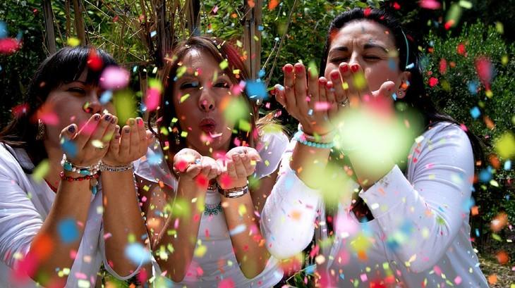 שלוש נשים נושפות חתיכות נייר צבעוניות אל המצלמה