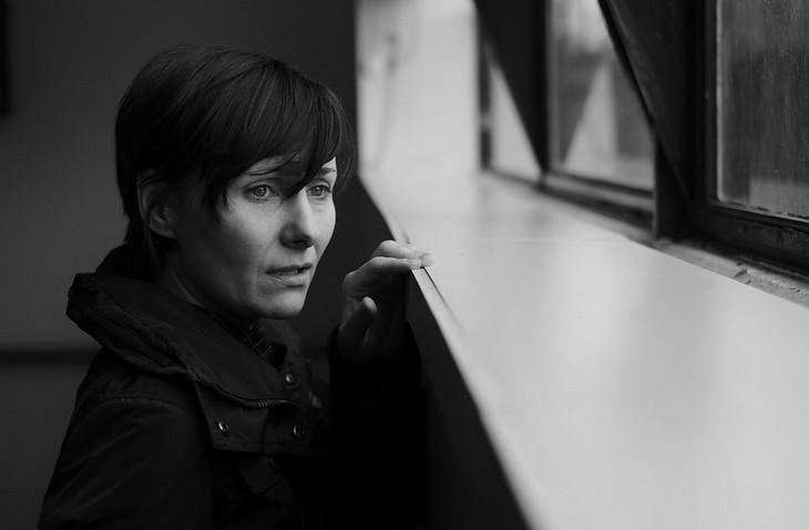 אישה עצובה מסתכלת  החוצה מאדן החלון